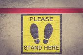 image of slip hazard  - PLEASE STAND HERE foot sign or symbol on the floor Retro filter effect - JPG