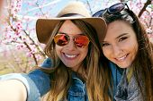 pic of two women taking cell phone  - Portrait of two beautiful young women taking a selfie in the field - JPG
