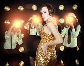 image of superstars  - Superstar woman wearing golden shining dress posing to paparazzi - JPG