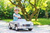stock photo of preschool  - Little preschool boy driving big toy old vintage car and having fun outdoors - JPG