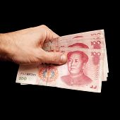 picture of yuan  - Chinese 100 yuan renminbi banknotes in male hand isolated on black background - JPG