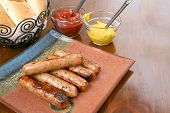 image of condiment  - Grilled brats on a stacked on a plate ready to serve with condiments ketchup and mustard and buns - JPG
