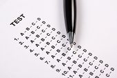 picture of bubble sheet  - close up of test score sheet with answers and metal pen - JPG