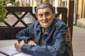 picture of disability  - Elderly disabled man with cerebral palsy writing in notebook - JPG