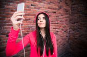 stock photo of sportive  - Happy young sportive woman making selfie photo with smartphone over brick wall - JPG