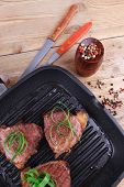picture of bloody  - fresh grilled bloody beef steaks on black grill plate on wood - JPG