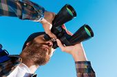 image of long beard  - Long angle view of handsome young bearded man looking through binoculars away  - JPG