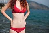 stock photo of bathing  - travel body of the girl in a bathing suit near the sea - JPG