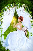 pic of wedding arch  - Beautiful bride with chaming red hair sitting under the wedding arch - JPG