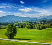 stock photo of bavarian alps  - Road in pastoral idyllic german countryside with Bavarian Alps in background on beautiful summer day - JPG