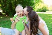 stock photo of mums  - Happy family outdoors mum and dad hold and kiss baby focus on kid - JPG