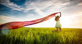 picture of jumping  - Young lady runing with tissue in green field - JPG