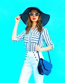 Fashion Portrait Young Woman Wearing A Straw Hat, White Pants And Handbag Clutch Over Colorful Blue poster