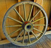 stock photo of stagecoach  - An Old Wagon Wheel rests inside a Wooden Barn - JPG