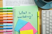 Notebook with text WHAT IS MARKETING on table poster