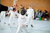 Little Kid Boy Fencing On A Fence Competition. Child In White Fencer Uniform With Mask And Sabre. Ac poster