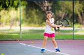 Child Playing Tennis On Outdoor Court poster
