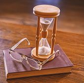 Time Flow Concept. Hourglass, Old Book And Eyeglasses On Wooden Table, Wooden Background.wooden Hour poster