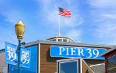 Usa American Flag Above Historic Pier 39, San Francisco, California . Blue Sky poster