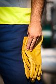 man holding yelow gloves
