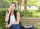 Melancholy Young Adult Woman Sitting on Bench Next to Books and Backpack.