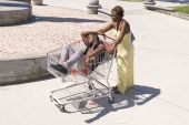 stock photo of inference  - A woman pushes her passed out husband down a walkway in a shopping cart - JPG