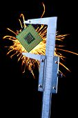 image of microprocessor  - microprocessor clamped in a caliper with sparks on a background - JPG