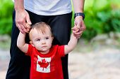 picture of lost love  - Toddler lost in thought wearing a Canadian maple leaf shirt walking assisted by his father - JPG