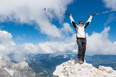 picture of ascending  - Female climber standing on top of a mountain and celebrating her successful ascend - JPG