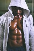 stock photo of down jacket  - Muscular young man in hood jacket at the gym - JPG