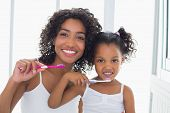 foto of oral  - Pretty mother with her daughter brushing their teeth at home in the bathroom - JPG