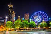 image of ferris-wheel  - Ferris wheel and buildings seen from Olympic Centennial Park at night in Atlanta Georgia - JPG