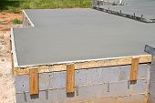 stock photo of cinder block  - New construction of a freshly poured concrete slab floor on a residential home cures and hardens - JPG