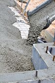 picture of chute  - Wet cement pours down a concrete truck chute to fill a slab at a home building construction site - JPG