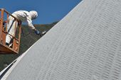 image of cherry-picker  - Tradesman spray painting the roof of an industrial building - JPG