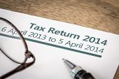 foto of self assessment  - UK Income tax return form for 2014 on a desk with pen and glasses - JPG