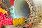 picture of pipe-welding  - Welder welding a pipe on a terrain