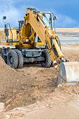 picture of wheel loader  - Wheel loader excavator parked at construction site  - JPG