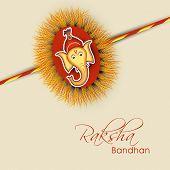 picture of rakhi  - Beautiful rakhi decorated with Hindu mythology Lord Ganesha face on brown background for Happy Raksha Bandhan - JPG