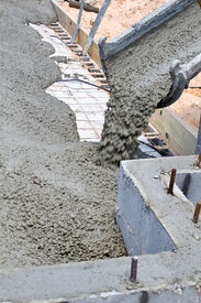 image of chute  - Wet cement pours down a concrete truck chute to fill a slab at a home building construction site - JPG