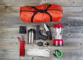 image of personal safety  - Overhead view of hiking gear and personal protection pistol and knife placed on rustic wood - JPG