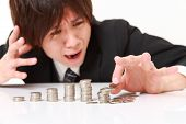 picture of japanese coin  - stack of coins collapsed when businessman put a coin - JPG