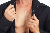 image of undressing  - Young man undresses his black shirt close up - JPG