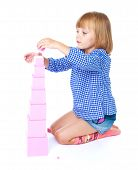 picture of montessori school  - charming little girl collects in the Montessori classroom pyramid isolated on a white horse - JPG