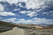 stock photo of manali-leh road  - View Of Curved Road Among Snow Capped Mountains - JPG