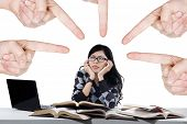 stock photo of stop bully  - Portrait of female student being bullied by big fingers symbolizing student bullying - JPG