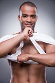 foto of toothless smile  - Handsome young African man taking off his tank top and smiling while standing against grey background - JPG