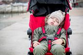 stock photo of seatbelt  - Toddler child is sleeping in the stroller outdoors - JPG