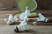 picture of shuttlecock  - Shuttlecock and Racket with parts of its feathers scattered on wood