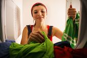 image of housekeeping  - Young hispanic woman at home doing chores and housekeeping collecting clothes from laundry tumble drying machine